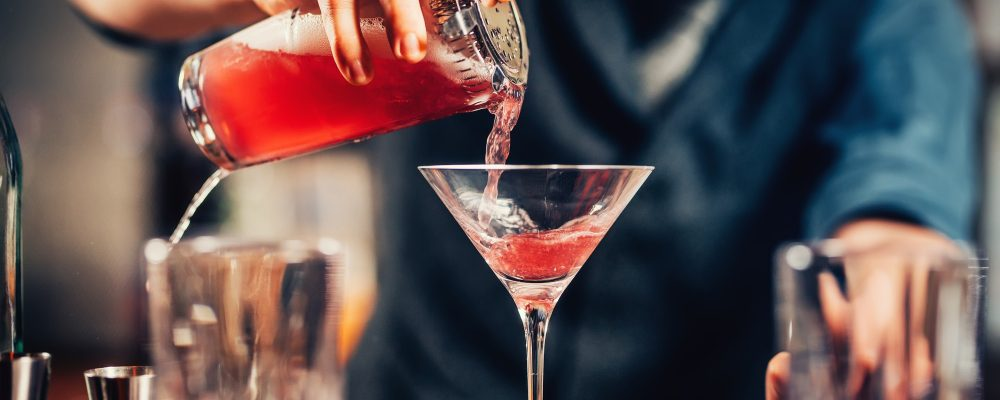 Close up details of barman pouring vodka cosmopolitan cocktail in martini glass