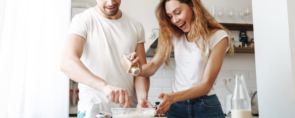 Image of gorgeous couple cooking and mixing dough in kitchen at home